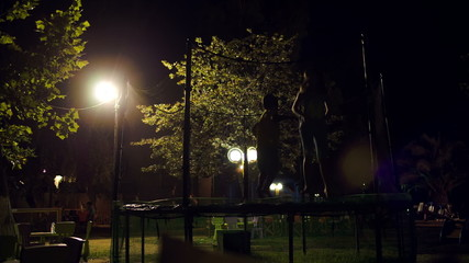 Children jumping on trampoline at night