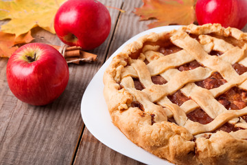 Homemade apple pie, apples and autumn leaves
