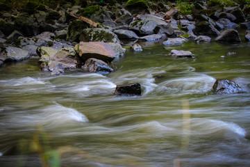 Steine im kalten sauberen klaren Gebirgsbach