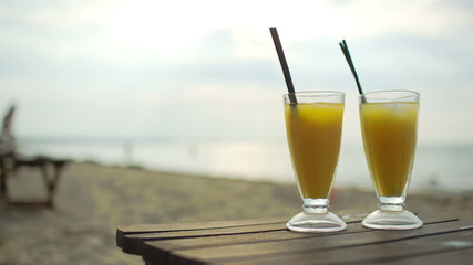 Two cocktails on wooden table by the sea