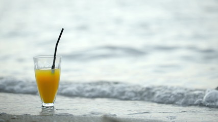 Glass of cocktail on beach and waves washing shore