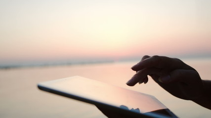 Female hands typing on tablet PC by sea at sunset