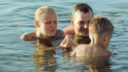 Parents and son in sea during summer vacation