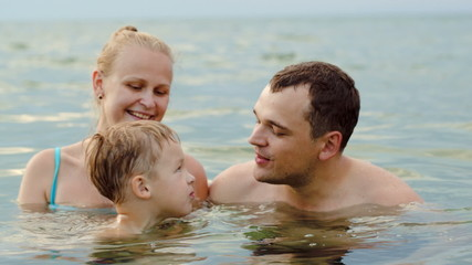 Lovely family with child bathing in sea