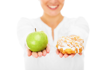 Woman showing apple and donut