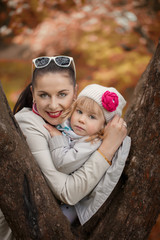 Portrait lovely mom and daughter in warm  sunny autumn day