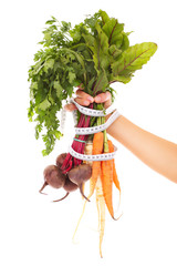 Vegetables tape measure and hand