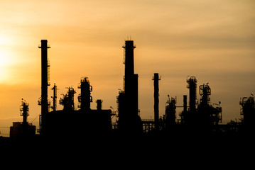 silhouette tower of oil refinery at sunrise