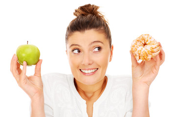 Woman choosing between apple and donut