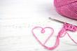Leinwandbild Motiv pink crochet background with yarn heart