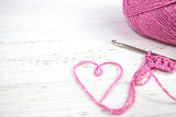 pink crochet background with yarn heart