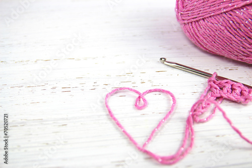 Fotobehang Ontspanning pink crochet background with yarn heart