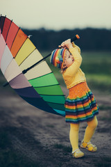 little girl with rainbow umrella in the field