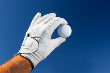 Hand wearing golf glove holding a white golf ball