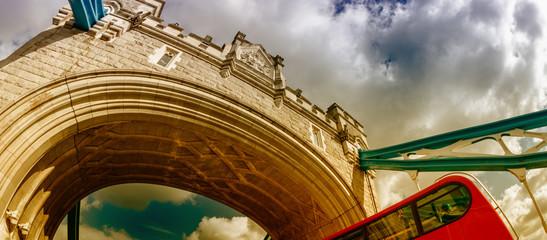 Red Double Decker Bus speeding up under Tower Bridge