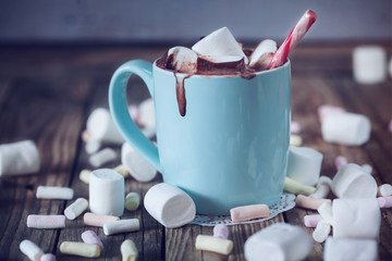 Mug filled with hot chocolate and marshmallow  and candy, toned