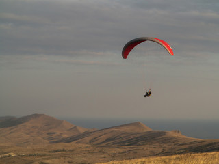 Paragliding. Hang glider flying over mountains.