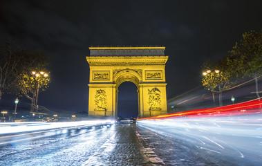 Traffic flow in Paris. Car light trails in front of Arc de Triom