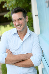 Smiling 40-year-old man leaning on home wall