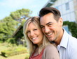 Cheerful mature couple standing in front of house