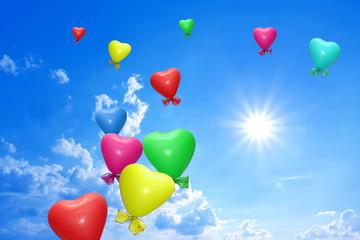 bunte Luftballonherzen am strahlend blauen Himmel