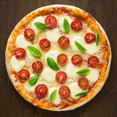 Pizza Margherita on dark wooden background top view