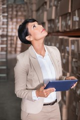 Pretty warehouse manager looking up holding tablet pc