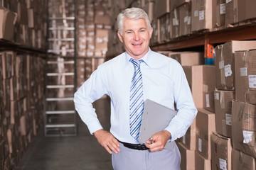 Smiling warehouse manager looking at camera