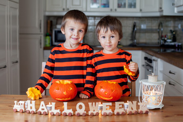 Two boys at home, preparing pumpkins for halloween