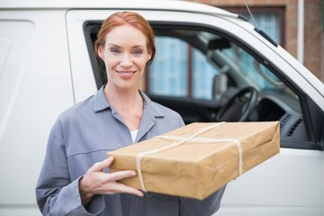 Delivery driver smiling at camera by her van holding parcel