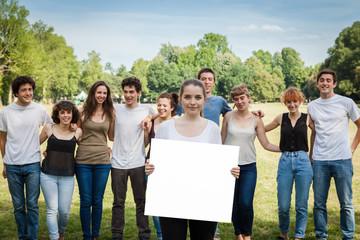 Gruppo di amici al parco.Una ragazza tiene un cartellone bianco