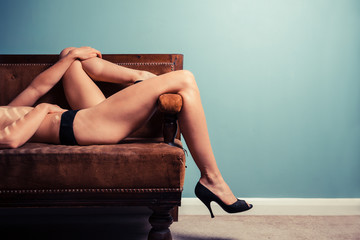 Sexy young woman in heels on a sofa