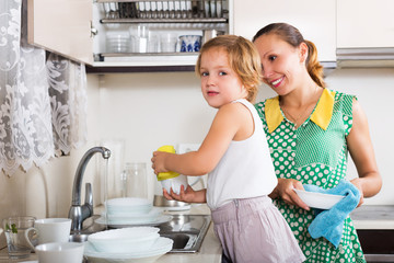 Daughter with mother washing plates