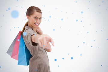 Side view of smiling woman pointing with shopping bags
