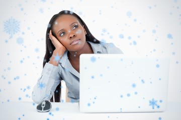 Businesswoman day dreaming while using a laptop