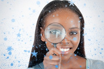Composite image of young woman with magnifier