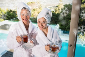 Smiling women in bathrobes having tea