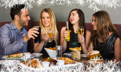 Composite image of friends having dinner together and toasting