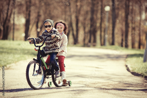 little girl and boy riding on bicycle together - 70529598