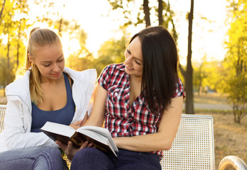 Two  happy girls reading book