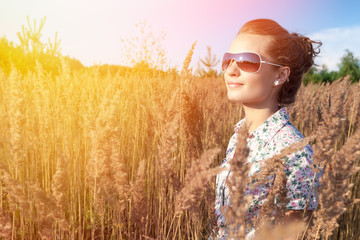 Beautiful girl in sunglasses on the nature in the sunshine