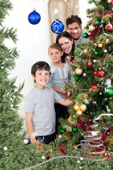 Family decorating a christmas tree with boubles