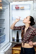 Girl drinks yogurt near an open refrigerator
