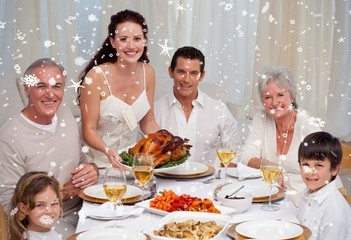 Composite image of family eating turkey in a dinner