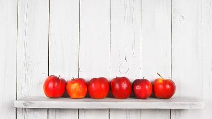 Apples on a wooden shelf.