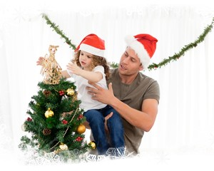 Cute daughter decorating the christmas tree with his father