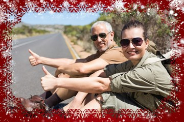 Hitch hiking couple sitting on the side of the road