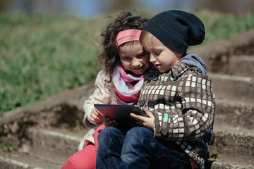 boy and girl using tablet