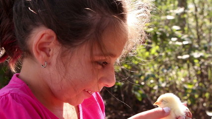 Cute girl kissing and petting little yellow chicken, close up