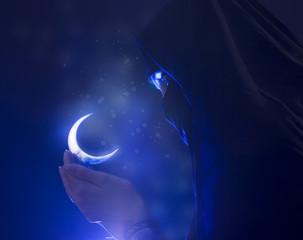 Beautiful young muslim girl holding a moon symbol, spirituality